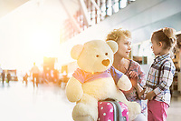 Portrait of mother reuniting with her daughter in airport with lens flare