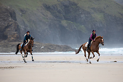 © Licensed to London News Pictures. 04/07/2020. Perranporth, UK. Tina Wallace (L) and Emily Dunstan (R) ride horses along Perranporth beach in Cornwall today, despite wet weather. Today marks a lift in COVID-19 restrictions, as pubs are allowed to open, whilst customers must still follow social distancing guidelines. Tens of thousands of tourists are due to arrive in Cornwall over this weekend, as overnight stays within England are also allowed. Photo credit : Tom Nicholson/LNP