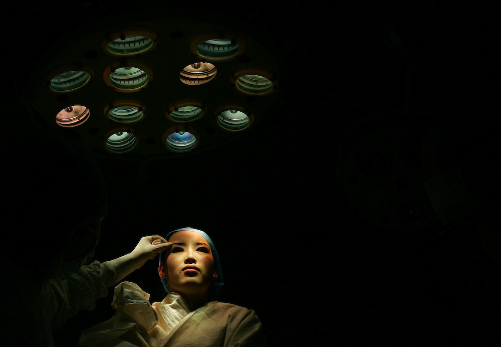 A Plastic surgeon looks at an eyelid surgery procedure done on a young inner Mongolian immigrant in Beijing, China Oct. 26, 2005. An Estimated one million Chinese people per year flocking to plastic surgery as a way to boost their confidence as expendable incomes grow. .Fueling the trend is a desire to compete in a rapidly changing society where image and first impressions count and social stigmas on buying perfection are few. A few decades ago, a Chinese woman could have been denounced and maybe even beaten for wearing lipstick, much less undergoing surgery to improve their looks. In the 1960s and 1970s, the closest thing to a Chinese beauty ideal was Liu Hulan, a robust 15-year-old country girl with a practical bob and not a trace of makeup who was decapitated by the Nationalists when she refused to name her fellow Communists in 1947..