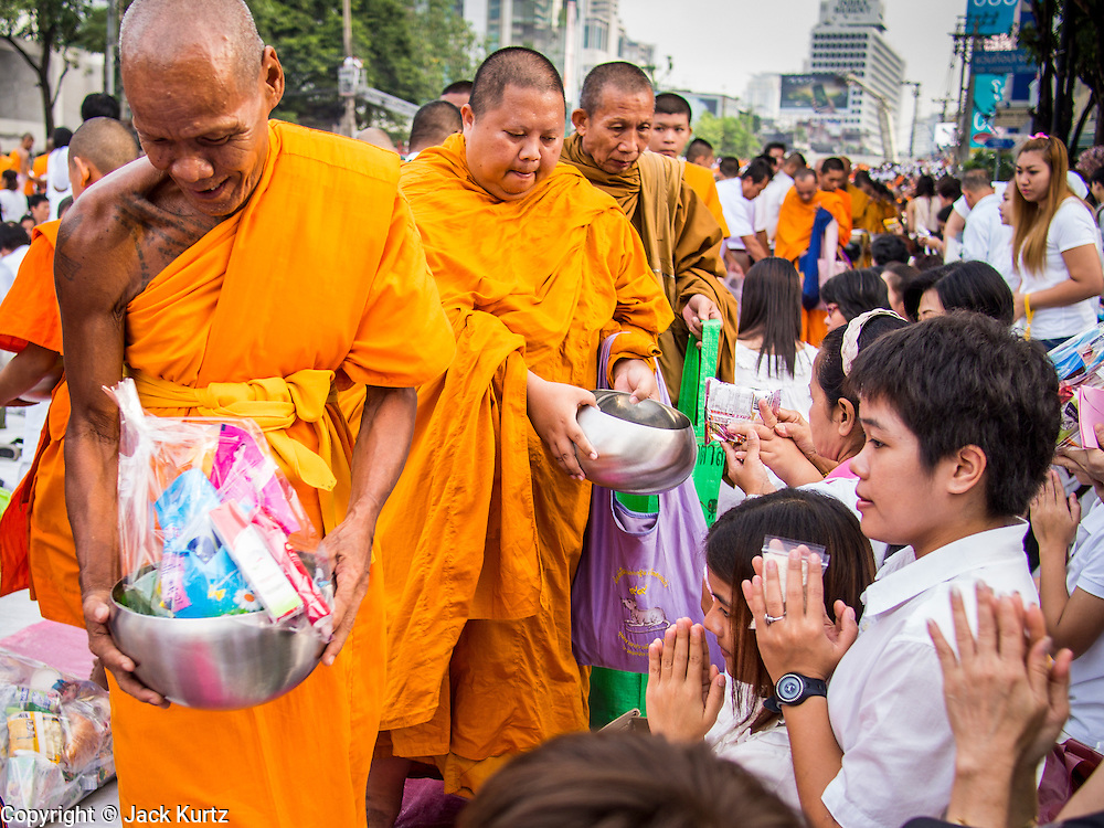 08 SEPTEMBER 2013 - BANGKOK, THAILAND: People pray as Buddhist monks walk past them during a mass alms giving ceremony in Bangkok Sunday. 10,000 Buddhist monks participated in a mass alms giving ceremony on Rajadamri Road in front of Central World shopping mall in Bangkok. The alms giving was to benefit disaster victims in Thailand and assist Buddhist temples in the insurgency wracked southern provinces of Thailand.  PHOTO BY JACK KURTZ