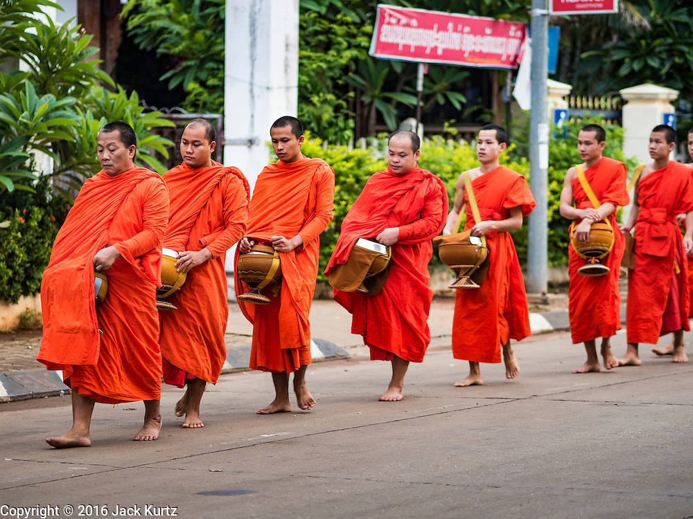 16 JUNE 2016 - PAKSE, CHAMPASAK, LAOS:  Buddhist monks on the morning Tak Bat, or alms rounds in Pakse. The monks walk through the community just after sunrise accepting alms from people. Pakse is the capital of Champasak province in southern Laos. It sits at the confluence of the Xe Don and Mekong Rivers. It's the gateway city to 4,000 Islands, near the border of Cambodia and the coffee growing highlands of southern Laos.     PHOTO BY JACK KURTZ