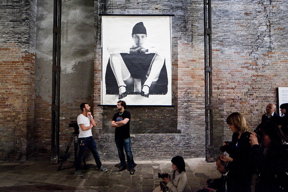 VENICE, ITALY - 31 MAY 2013: Visitors are here nearby Elisabetta Catalano's photograph during Fabio Mauri's &quot;Ideologia e Natura&quot; - performance -  at the Italian Pavillon, at the Arsenale of the Biennale in Venice, Italy, on May 31st 2013. <br /> <br /> The Italian Pavilion presents vice versa, an ideal journey through Italian art of today,<br /> an itinerary that tells of identities, history and landscapes - real and imaginary - exploring the complexity and layers that characterize the country's artistic vicissitudes. The Italian Pavillon is curated by Bartolomeo Pietromarchi,<br /> who describes the exhibition as, ?A portrait of recent art, read as an atlas of themes and attitudes in dialogue with the historical legacy and current affairs, with both a local and international dimension. A cross-dialogue of correspondences, derivations and differences between acclaimed maestros and artists of later generations&quot;. The exhibition is divided into seven spaces - six rooms and a garden - that each house<br /> the work of two artists,<br /> who are brought together on the basis of the affinity of their<br /> respective poetics and common interests in themes, ideas and practices.<br /> <br /> The 55th International Art Exhibition of the Venice Biennale takes place in Venice from June 1st to November 24th, 2013 at the Giardini and at the Arsenale as well as in various venues the city. <br /> <br /> Gianni Cipriano for The New York TImes