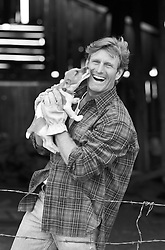 All American man being licked by a Jack Russell puppy in a barn