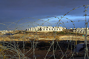 A Jewish settlement in Palestine. Looking at it through a barbed wire barrier of the security fence.