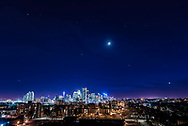 Orion and the stars of winter setting over the downtown core of Calgary, on April 19, 2018.<br /> <br /> I shot this from Tom Campbell Park, looking west. Venus is the bright object at far right; Sirius is the bright star at far left, with both flanking the skyline. Above is the waxing crescent Moon. The Pleiades is above Venus. <br /> <br /> This is a stack of 4 x 2-second exposures taken for a time-lapse and star trail set, all with the 24mm Sigma Art lens at f/2.8 and Nikon D750 at ISO 400. The Moon is from an HDR-blend of shorter exposures so its disk does not overexpose into a bright blob in the thin cloud. It better depicts the scene the way the eye saw it, though in this case the camera is picking out stars better than the eye could with all the foreground lighting and glare. <br /> <br /> No light pollution filter was employed.