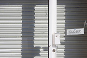A closed sign is stuck to the glass and metal shutters have been rolled down in a shop window in Weston-super-Mare, a victim of the UK recession.
