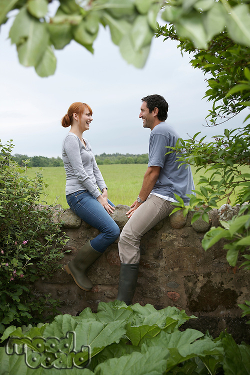 Couple sitting on wall in countryside
