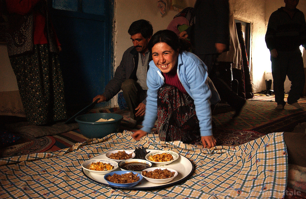 Ali Ipak's daughter Emel, 17, (in blue) offers tea to her father (far left), a neighbor Kazim Kardes, and the mayor of Kutoren Mr Ugur Akdogan  (in suit)   December 13, 2005 in central Turkey, Konya in Kutoren district, about 400 kilometers from Ankara. (Ami Vitale)
