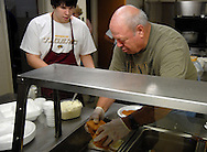 25 MARCH 2011 -- LEMAY, Mo. -- Matt Glozier (left) and Jim Van Der Haar restock fish on the serving line during the fish fry at St. Andrew Catholic Church in Lemay, Mo. Friday, March 25, 2011. Volunteers served more than 600 meals Friday and ran out of the parish's signature macaroni and cheese, said Karen Wood, one of the parishioners who helps organize the fish fry. Image © copyright 2011 Sid Hastings.