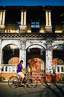 Jaffna, Sri Lanka -- February 8, 2018: A woman rides her bicycle past an old building.