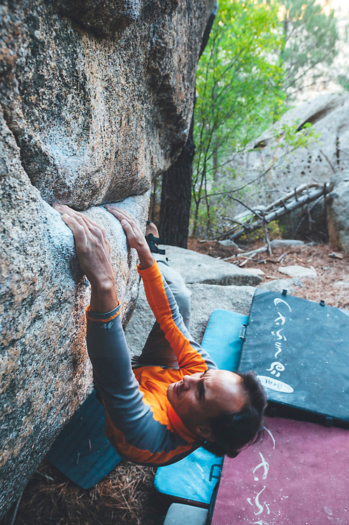 Climbers practicing boulder in granite forest in La Pedriza, Spain
