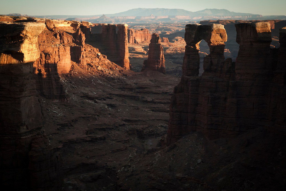 Sunset view of a sandstone arch while touring the White Rim Trail near Moab, Utah.