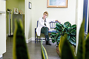 Female doctor in white lab coat sitting with legs crossed with plant in foreground in the lobby of a medical office, Tucson, Arizona...Media Usage:.Subject photograph(s) are copyrighted Edward McCain. All rights are reserved except those specifically granted by McCain Photography in writing...McCain Photography.211 S 4th Avenue.Tucson, AZ 85701-2103.(520) 623-1998.mobile: (520) 990-0999.fax: (520) 623-1190.http://www.mccainphoto.com.edward@mccainphoto.com