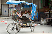 A pedicab driver waits barefoot for customers on a street corner  in Longnan, China.