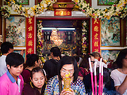 16 SEPTEMBER 2016 - BANGKOK, THAILAND: People pray in the entrance to  Heng Chia Shrine on Chareon Krung Road during the Mid-Autumn Festival in Bangkok. The festival was originally a time to enjoy the successful reaping of rice and wheat and is still celebrated as a harvest festival in agricultural communities. In Bangkok, people make food offerings in honor of the moon. And it is an opportunity to share mooncakes.   PHOTO BY JACK KURTZ