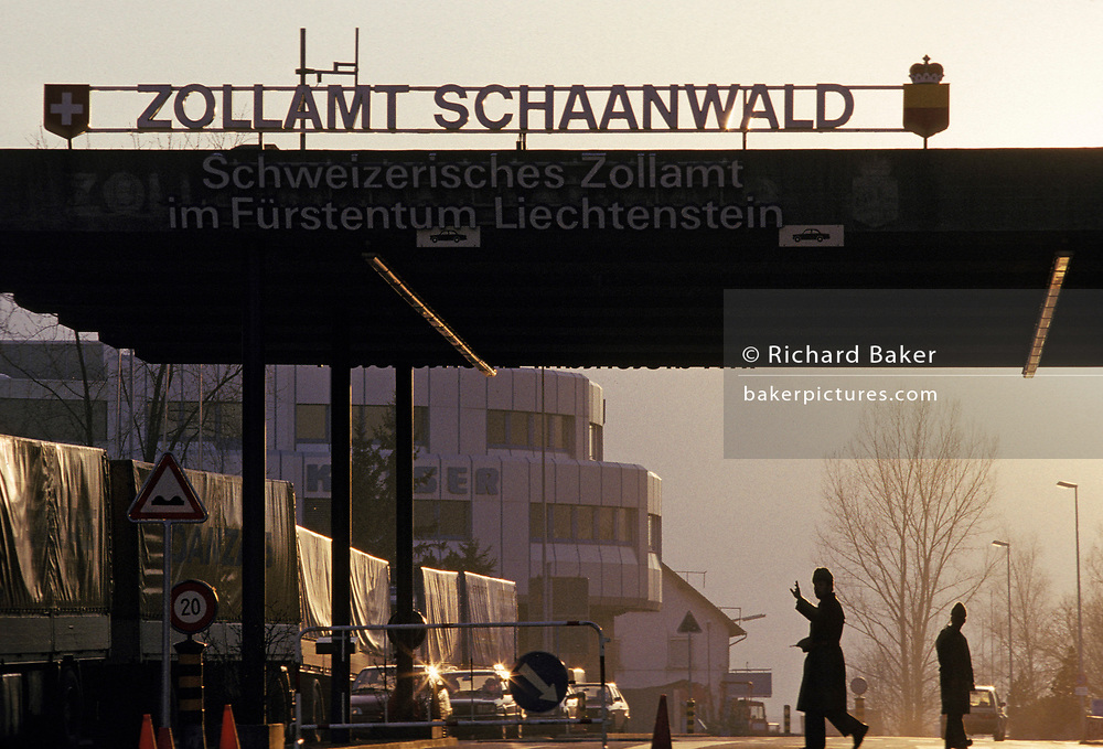 A customs officer holds up a hand to traffic passing through the national border between Liechtenstein and Austria, what the Austrians call a 'Zoll' or 'Zollamt' at Schaanwald, the north-eastern line near the Austrian town of Feldkirch, on 8th February 1990, in Schaanwald, Austria.