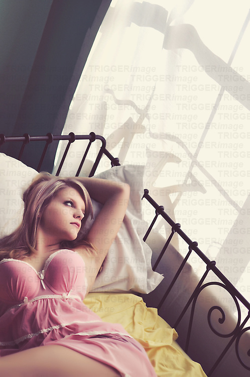 Close up of a sexy young woman with blonde hair lying alluringly on a bed