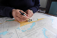 Captain calculates sailing coordinated in Antarctica on a map.