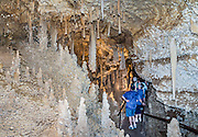 "People admire ornate natural decorations in Caverns of Sonora, Sutton County, Texas, USA. The world-class Caverns of Sonora have a stunning and sparkling array of speleothems (helictites, stalactites, stalagmites, flowstone, coral trees, and other calcite crystal formations). National Speleological Society co-founder, Bill Stephenson said, after seeing it for the first time, ""The beauty of Caverns of Sonora cannot be exaggerated...not even by a Texan!"" Geologically, the cave formed between 1.5 to 5 million years ago within 100-million-year-old (Cretaceous) Segovia limestone, of the Edward limestone group. A fault allowed gases to rise up to mix with aquifer water, making acid which dissolved the limestone, leaving the cave. Between 1 and 3 million years ago, the water drained from the cave, after which speleothems begain forming. It is one of the most active caves in the world, with over 95% of its formations still growing. Sonora Caves are on Interstate 10, about half-way between Big Bend National Park and San Antonio, Texas."
