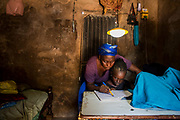 SIPANE - SENEGAL: A mother helps her daughter with homework at a room lit up with a solar lamp unit at Sipane village on August 02 2017 in Sipane, Senegal. Despite the high growth and expectations on Senegalese economy, many rural areas still live without power.
