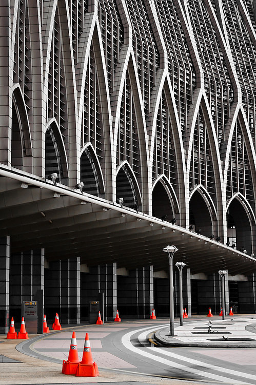 Stock photograph of the Ministry of Finance Building in Putrajaya, Malaysia. The orange safety cones stand out against the monotone abstract lines of the building.