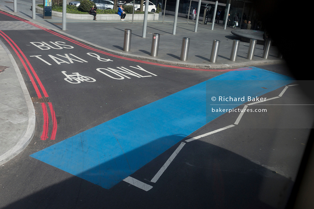 A blue strip awaiting stencilled lettering stretches across the junction at the south side of Westminster Bridge, on 6th April 2018, in London, England.
