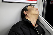 man asleep while commuting Japan