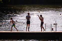 Men and boys enjoy the refreshing water at the men's swimming pond at Hampstead Heath in London. London, July 25 2019.