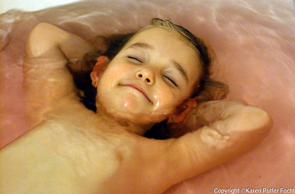 A young girl is content in the bathtub.