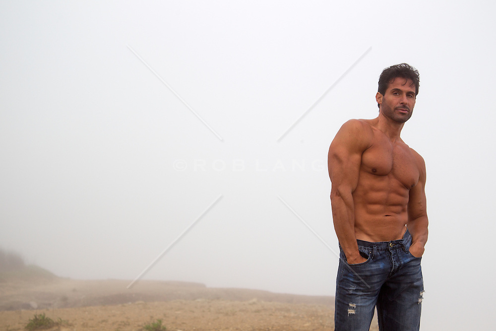 handsome shirtless man with hands in his pockets outside