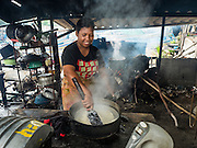 15 JUNE 2105 - NARATHIWAT, NARATHIWAT, THAILAND:  A women cooks rice over wood fired stoves near the fishing port in Narathiwat.      PHOTO BY JACK KURTZ