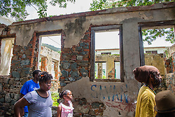 Children look at the remains of an old building ravaged by fire and left in ruin.  The Virgin Islands Economic Development Association Enterprise & Commercial Zone Commission hosts a historical tour through the Savan (Savanne) neighborhood.   St. Thomas, US Virgin Islands.  9 July 2015.  © Aisha-Zakiya Boyd