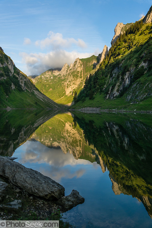 Hundstein peak reflects in Fälensee at sunrise, in the Alpstein limestone range, Appenzell Alps, Switzerland, Europe. Founded in 1903, Berggasthaus Bollenwees is a beautiful place to stay overnight in private double ensuite or dormitory rooms. A spectacular ridge walk covered in wildflower gardens starts at Hoher Kasten, reached via cable car from Brülisau, just 10 minutes bus ride from Appenzell village. For a wonderful day hike, take the lift; or arranging for overnight stay at Berggasthaus Staubern or Bollenwees allows time to ascend Hoher Kasten summit (1794 m) on foot. Appenzell Innerrhoden is Switzerland's most traditional and smallest-population canton (second smallest by area).