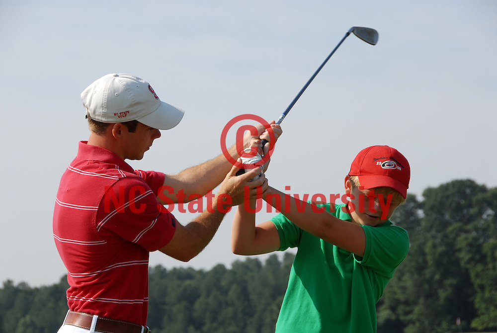 Instructor helps a camper with his grip at the Lonnie Poole Golf Course. PHOTO BY ROGER WINSTEAD