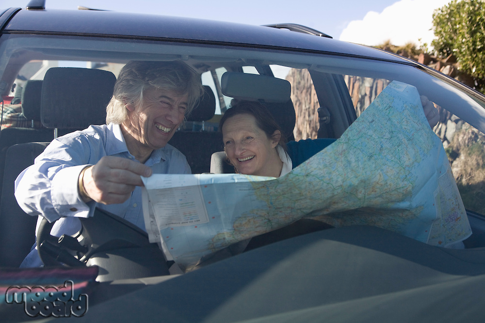 Mature couple laugh over a map