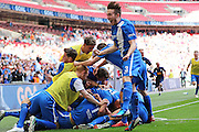 Glossop players celebrate the opening goal and Glossop Matthew Russell leaps in the air during the FA Vase Final between Glossop North End and North Shields at Wembley Stadium, London, England on 9 May 2015. Photo by Phil Duncan.