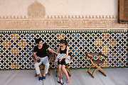 Asian tourists rest in courtyard of Nasrid Palace at Alhambra.