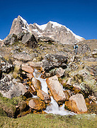 Nevado Cuyoc (Puscanturpa Sur, 5550 meters), trekker above a stream in Cuyoc Valley. Day 5 of 9 days trekking around the Cordillera Huayhuash in the Andes Mountains, Peru, South America.