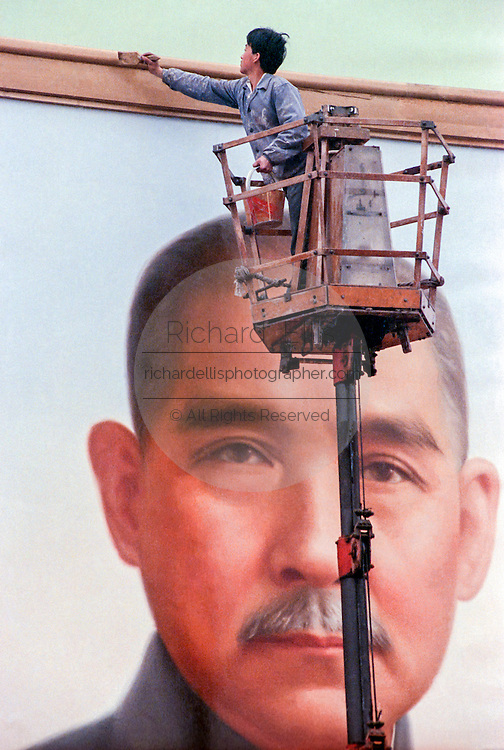 A worker touches up the frame of a giant portrait of Sun Yat-Sen erected in Tiananmen Square September 29, 1989 in Beijing, China. The portrait is installed in the square each year as part of the celebrations of China's National Day on October 1. Sun is considered the founder of modern China for his 1911 overthrow of the last imperial dynasty.