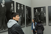 "New York, NY - 6 May 2016. Frieze New York art fair. Visitors among the large-scale silver-gelatin photos by Magnum photographer Chien-Chi Chang, from his series ""The Chain"", in the Chi-Wen Gallery of Taipei."