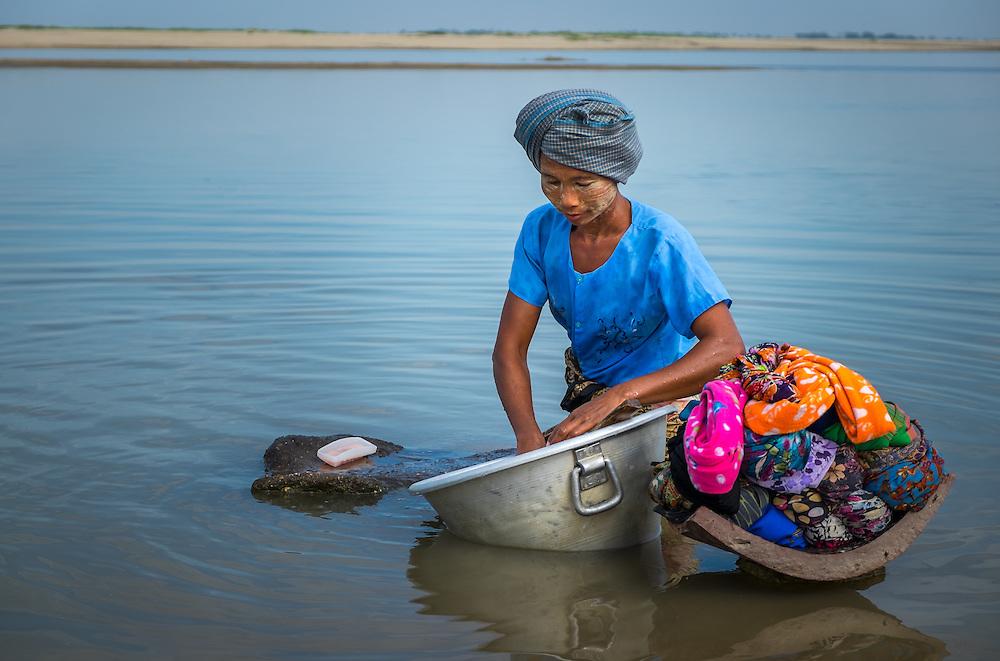 BAGAN, MYANMAR - CIRCA DECEMBER 2013: Burmese woman washing clothing by a river in a village near Bagan
