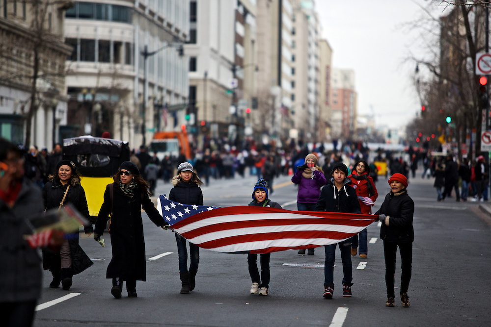 "Alida Yath, from right, and her family Francisco Ventura, 14, Kevin Huang Ventura, 9, Ingrid Huang Ventura, 11, Roxanne Ventura and Ingrid Ventura, arrive to the parade route with their own American flag before the inauguration parade for Pres. Barack Obama on January 21, 2013 in Washington, D.C. Yath, originally from Guatemala, became a U.S. citizen in August specifically so she could vote for Pres. Obama. ""I want better immigration laws, affordable education, health care and no more weapons,"" Yath said."