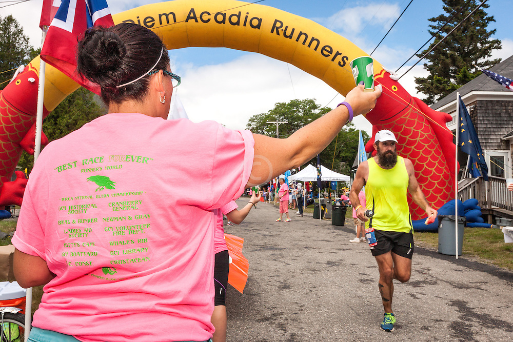 Great Cranberry Island Ultra 50K road race: race volunteer holds water for runner