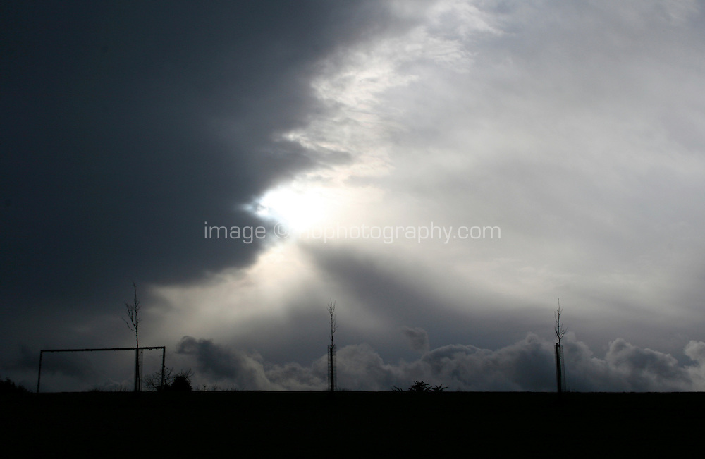 Silhouette of football goal posts and trees with dramatic grey clouds just before the rain at a park in Dublin Ireland