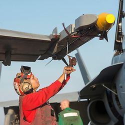 USS John C Stennis CVN-74 Aircraft Carrier.Pic Shows Flight and Hangar Deck personnel in the red shirts making sure the F-18 Super Hornets  aircraft are loaded with the correct weapons and ammunition
