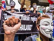 "02 JUNE 2013 - BANGKOK, THAILAND: A legless man clenches his fist while he leads a protest march through the Bangkok skywalk system. About 300 people wearing the Guy Fawkes mask popularized by the movie ""V for Vendetta"" and Anonymous, the hackers' group, marched through central Bangkok Sunday demanding the resignation of Prime Minister Yingluck Shinawatra. They claim that Yingluck is acting as a puppet for her brother, former Prime Minister Thaksin Shinawatra, who was deposed by a military coup in 2006 and now lives in exile in Dubai.      PHOTO BY JACK KURTZ"