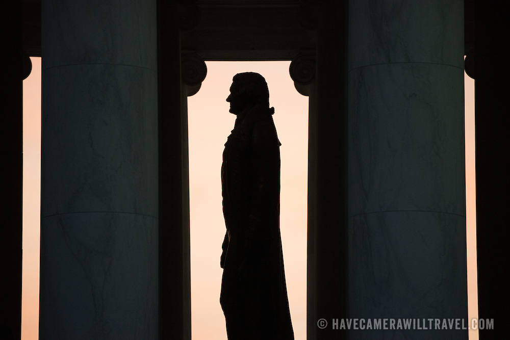 Washington DC--The large statue of Thomas Jefferson that stands in the middle of the Jefferson Memorial is silhouetted against the skies before dawn. The 19-foot high bronze statue of Thomas Jefferson was sculpted by Rudulph Evans. Opened in 1943 and designed by architect John Russell Pope, the Jefferson Memorial sits on an island on the southern bank of the Tidal Basin next to the Potomac and its Washington Channel.