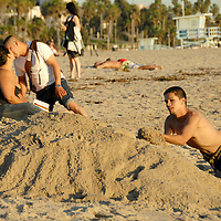 Gerardo Sandoval, 22 buries his brother Alex Espanoza, 12, in sand amid the sunset on Wednesday, October 27, 2010.