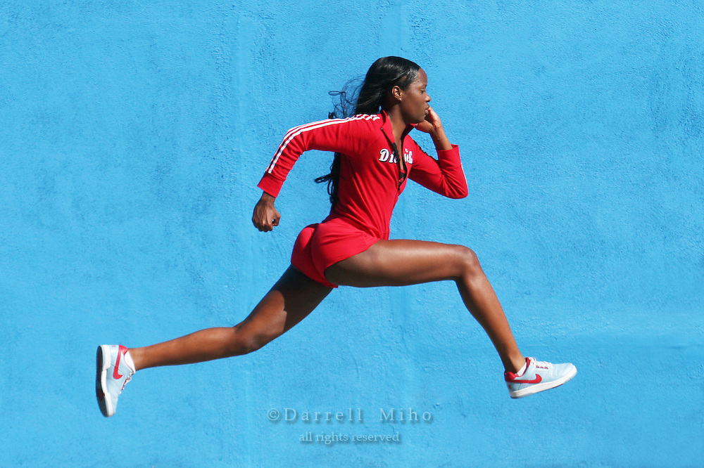 Model: LaKreshia Hart <br /> Running through the streets of LA wearing a red running outfit in front of a blue wall.<br /> <br /> Photo Credit Darrell Miho<br /> &copy; Darrell Miho