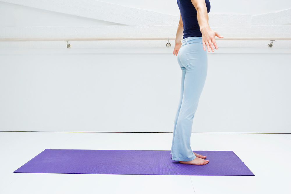 Young woman standing on a yoga mat warming up for her routine in a white room.